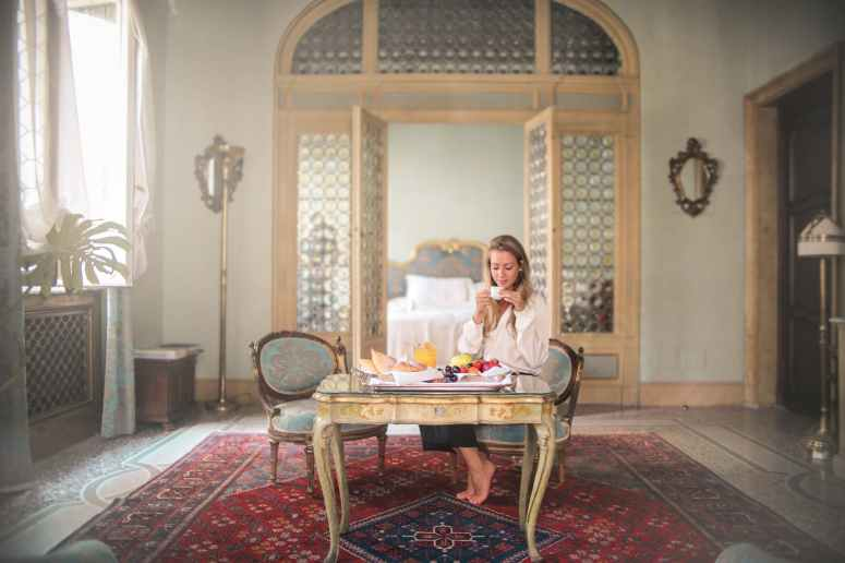 woman enjoying breakfast in luxury hotel room